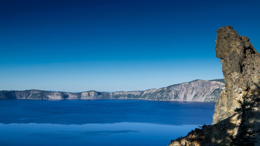 Panoramic view of the East side of blue Crater Lake from the Garfield Trail in the summer during the day, against cloudless, blue sky Volcanic Crater Volcano USA Oregon Crater Lake National Park Crater Lake, Oregon Crater Lake Outdoors Rock Formation Copy Space Mountain Clear Sky Tranquility No People Tranquil Scene Rock Nature Beauty In Nature Scenics - Nature Blue Sky Water