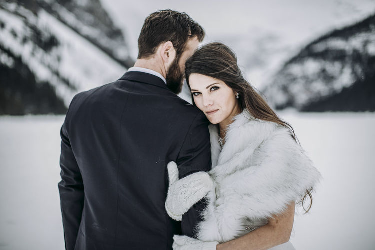 Young couple standing on snow during winter