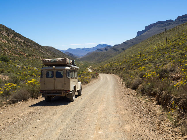 Classic 4x4 car on dirt track in in Cederberg Wilderness Mountain Area, South Africa 4x4 Cederberg South Africa Beauty In Nature Car Cedarberg Clear Sky Day Dirt Road Land Vehicle Mode Of Transport Mountain Mountain Range Nature No People Offroad Outdoors Road Scenics Sky The Way Forward Transportation Wild Flowers