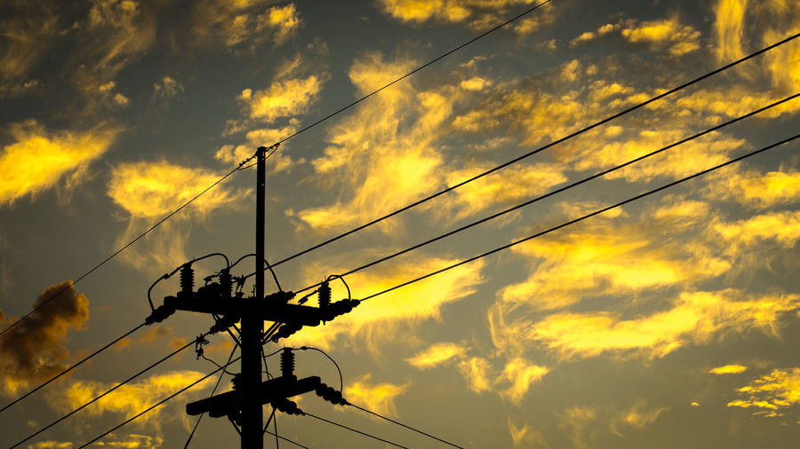 Low angle view of electricity pylon against orange sky
