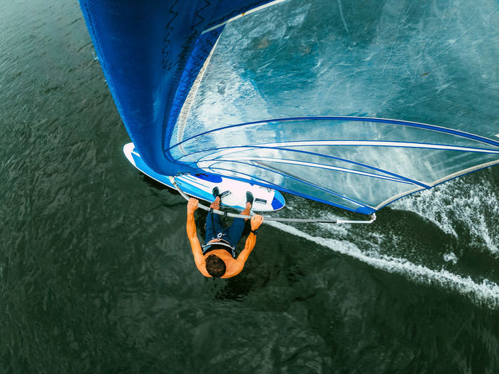 Wide-angle shot of adult man windsurfing on lake wallersee, austria