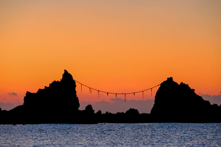 Silhouette built structure by sea against orange sky