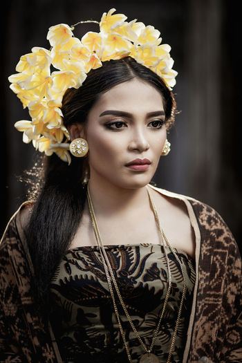 Close-up of young woman wearing flowers