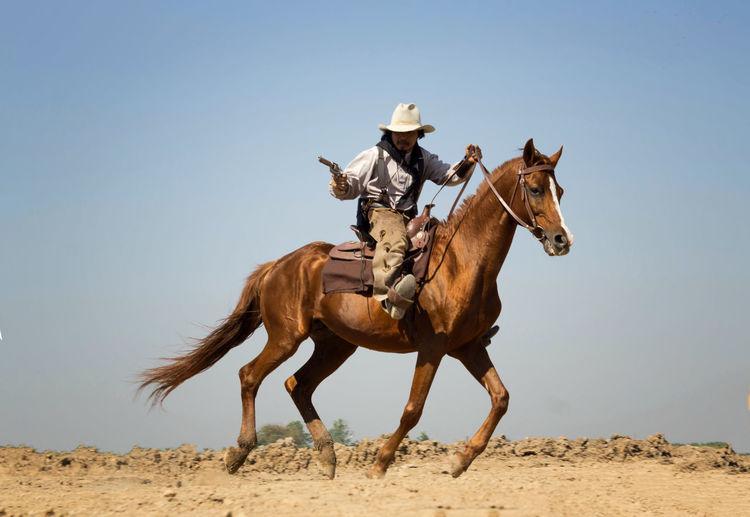 Man with gun riding horse against sky