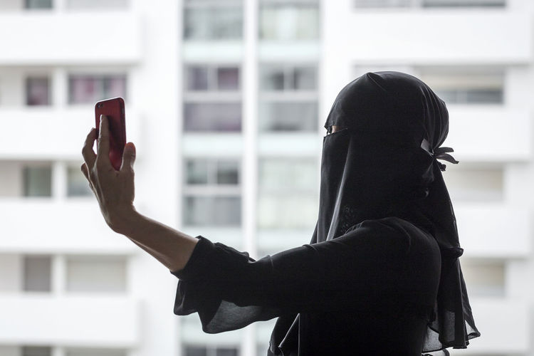Side view of woman in burka photographing by window in city