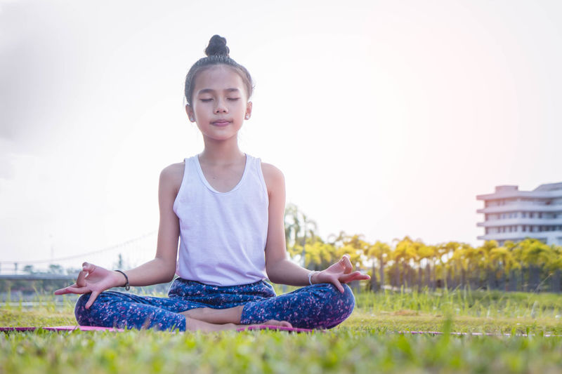 Yoga time the girl's Practice yoga Beautiful Woman Casual Clothing Contemplation Cross-legged Exercising Field Front View Full Length Grass Leisure Activity Lifestyles Lotus Position Meditating Nature One Person Outdoors Plant Posture Real People Relaxation Relaxation Exercise Sitting Yoga Young Adult