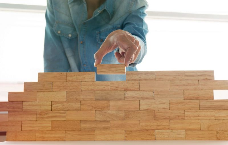 Midsection Of Man Arranging Wooden Blocks At Home