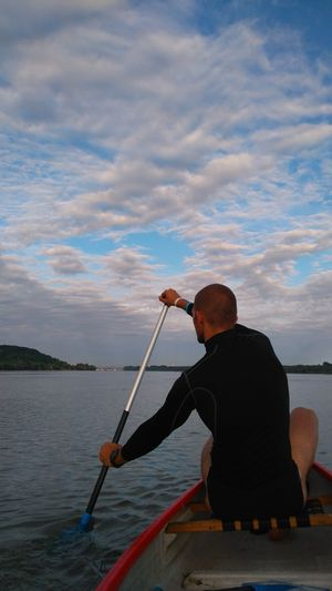 Rear View Of Man Rowing Boat At Sea Against Sky