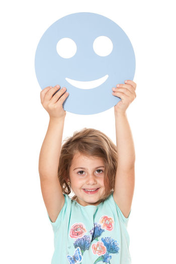 Young girl holding smiley face. All on white background. Child Childhood Curly Hair Girl Girlhood Happiness Happy Face Isolated On White Isolated White Background Kid One Person Positive Energy  Studio Shot Symbolic  White Background Young Girl
