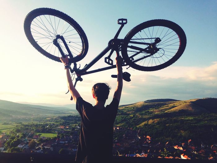 Rear View Of Man Lifting Bicycle Against Mountains