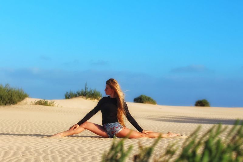 Young woman exercising on sand against sky
