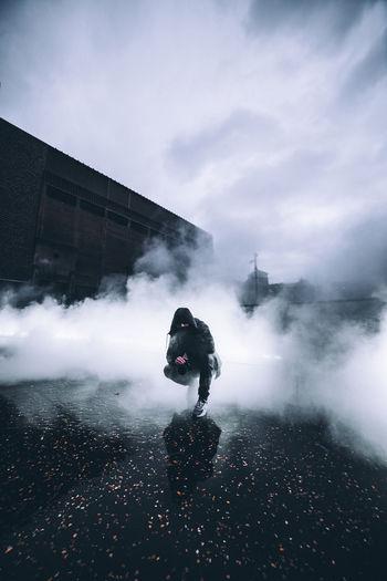 Man wearing hoodie standing amidst smoke on street