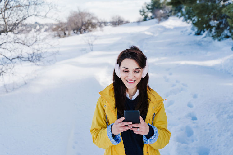 Young woman using phone while standing on snow