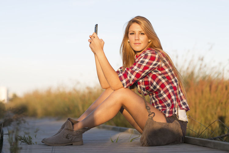 Beautiful young woman using smartphone in the field Adult Beautiful Woman Beauty Beauty In Nature Blond Hair Checked Pattern Day Full Length Holding Leisure Activity Lifestyles Long Hair Nature One Person Outdoors People Real People Relaxation Sitting Sky Smart Phone Technology Wireless Technology Young Adult Young Women