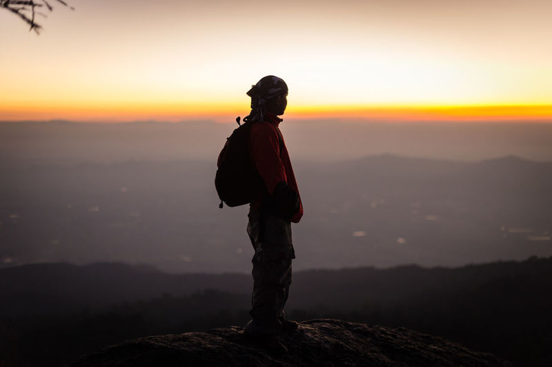 Rear view of man standing on rock at sunset