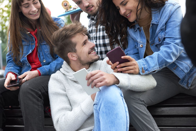 Happy friends using smart phone while sitting at park in city