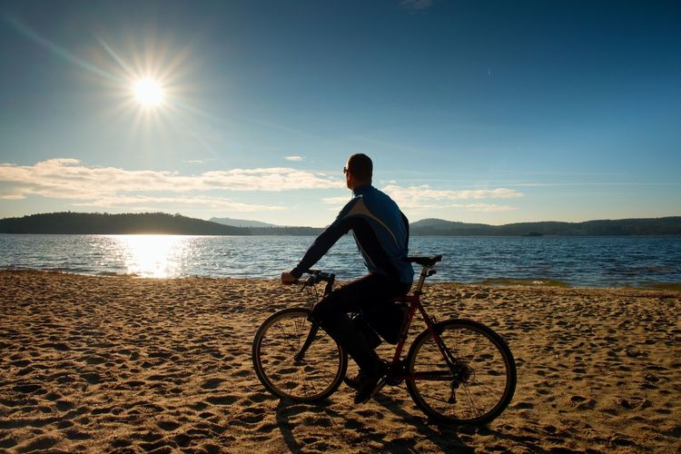 Young man cyclist sit on bike, blue sky and sunset background on beach. end of season at lake