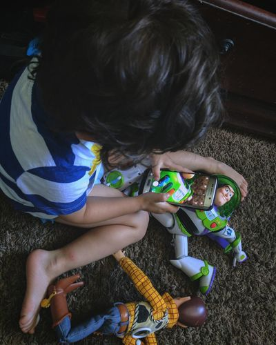 This kid is something else.... High Angle View One Person Child Childhood Children Only People Casual Clothing Indoors  Full Length Sitting Day Human Body Part Adult Close-up Full Frame Son Lifestyles Phone Toystory Woody Buzzlightyear Pixar  Roblsk