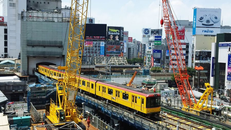 High angle view of train exiting shibuya hikarie with crane