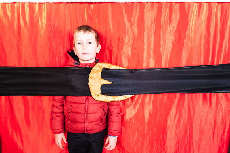 Portrait of cute boy standing against red curtain