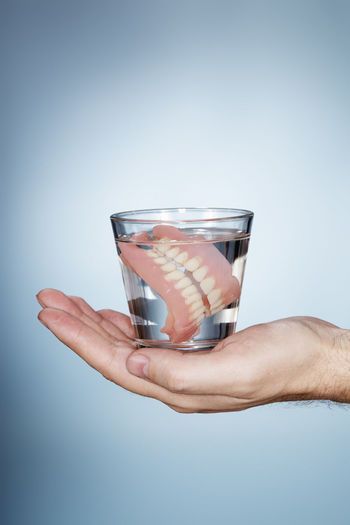 Man holding a glass containing old dentures. Artificial Dental Denture Dentures Drinking Glass Flame Glass Human Hand Liquid One Person Prostethic Studio Shot Teeth Water
