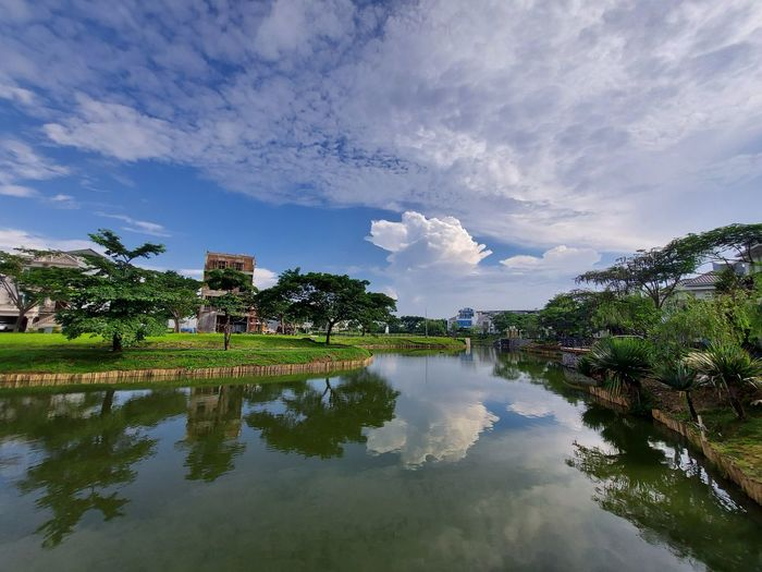 Scenic view of lake by trees and building against sky