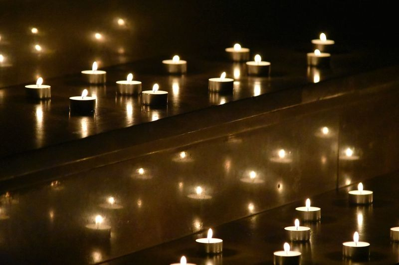 Illuminated candles against building