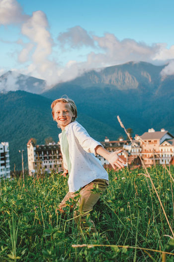 Portrait of smiling boy on mountain against sky