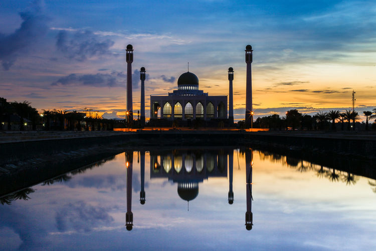 Reflection of mosque in lake during sunset