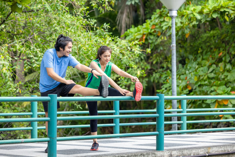 Full length of couple sitting on railing