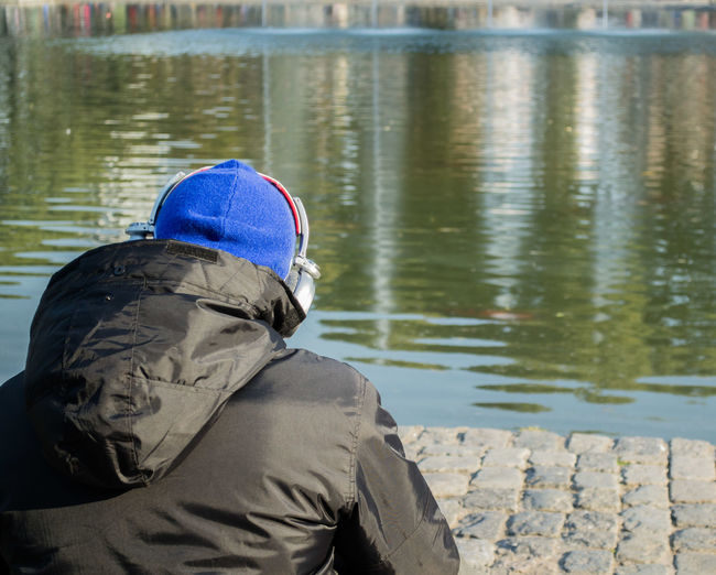 Rear view of man sitting by lake during winter