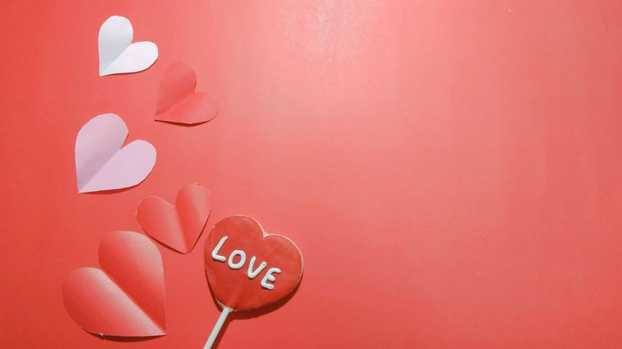 Close-up of heart shape against red wall