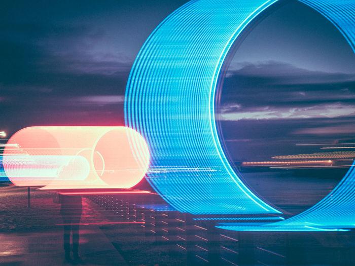 Digital composite image of illuminated ferris wheel against sky at night