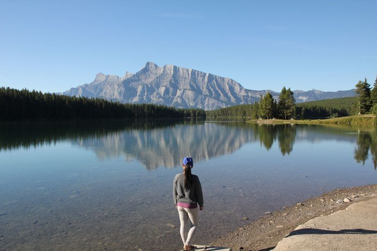 Beauty In Nature Blue Casual Clothing Clear Sky Day Full Length Getting Away From It All In Front Of Lake Leisure Activity Lifestyles Mountain Mountain Range Nature Non-urban Scene Reflection Remote Scenics Standing Standing Water Tourism Tranquil Scene Tranquility Vacations Water
