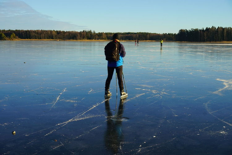 Rear view of man skating on frozen lake during winter