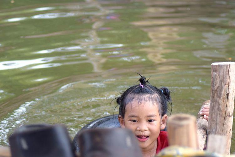 Smiling cute girl swimming in lake
