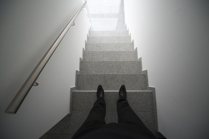 Man standing in a staircase Adult Adults Only Below Built Structure Day Directly Below Downhill Human Body Part Human Leg Indoors  Light Low Section Man One Man Only One Man Only. One Person People Personal Perspective Railing Staircase Stairs Stairways Standing Up Surrounding Wall Wall - Building Feature