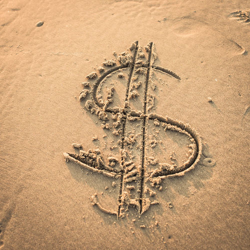High Angle View Of Dollar Sign At Beach