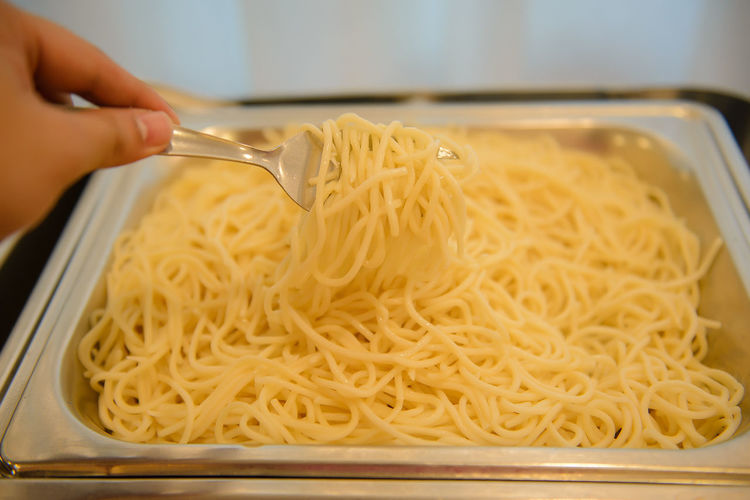 Cropped hand eating noodles