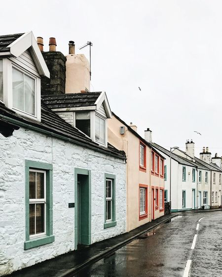 a hint of peach on a gloomy day Fishing Village Moody Sky Road Scotland The Week on EyeEm Weather Architecture Bird Building Exterior Built Structure Cottage Day House No People Outdoors Pastel Residential Building Small Town Small Town Stories Street Streetphotography Window