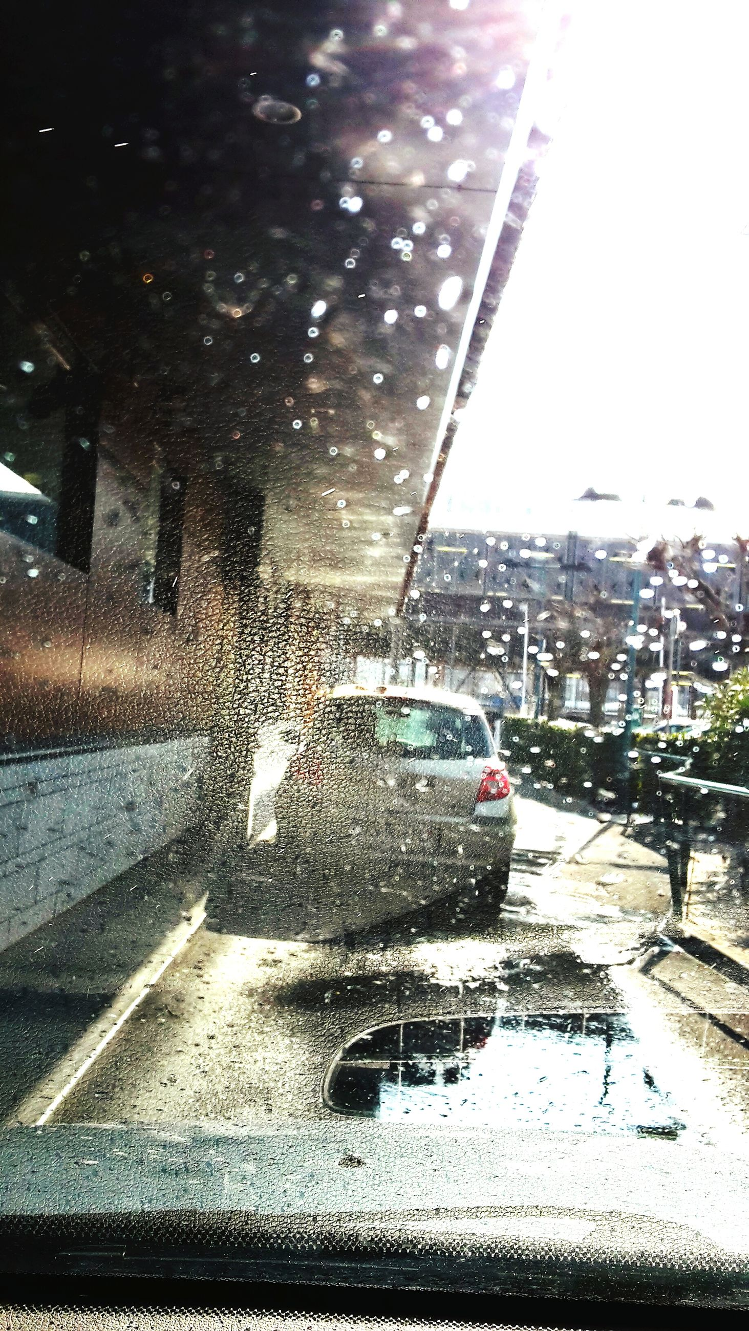 water, wet, transportation, rain, street, car, mode of transport, road, reflection, city, drop, season, glass - material, land vehicle, puddle, building exterior, transparent, motion, on the move, built structure