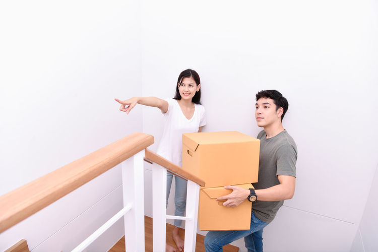 Young man with woman holding cardboard boxes at home