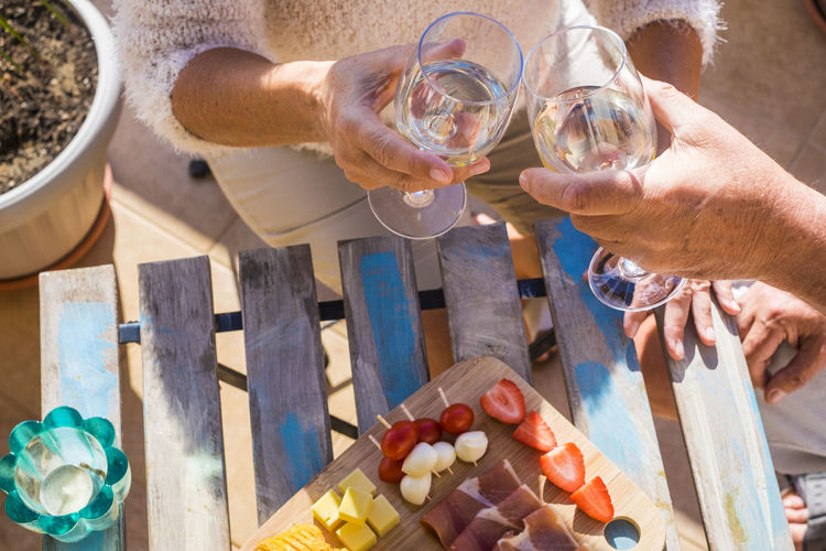 close up of two hands, a pair, from adult aged caucasian people do cheers with white wine and eat some fruits and snacks Drinking Drinking Glass Food Food And Drink Freshness Fruit Glass Hand Healthy Eating High Angle View Holding Human Body Part Human Hand Leisure Activity Lifestyles Men People Real People Refreshment Senior Couple Summer Two Hands Two People Vacation Wine