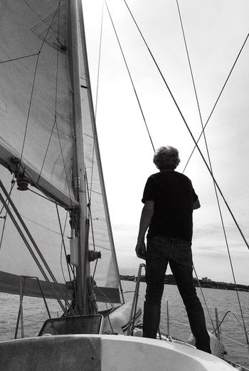 Rear view of man sailing on sea against sky