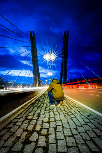 Rear view of woman sitting on bridge against sky at night