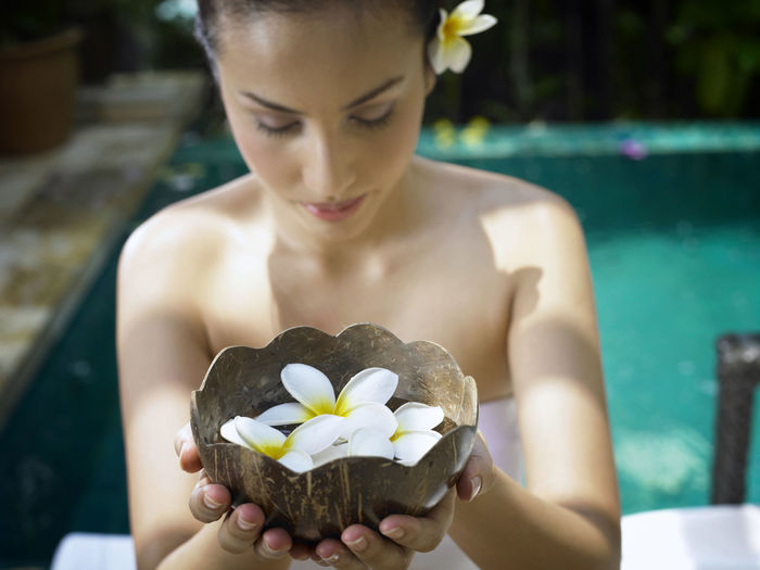 Woman holding frangipani in container at poolside