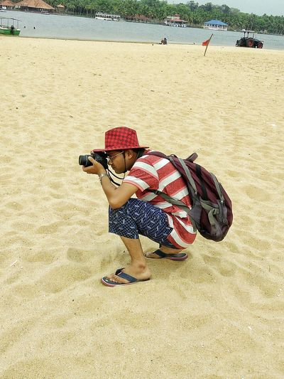 Man photographing through camera while crouching on sand at beach