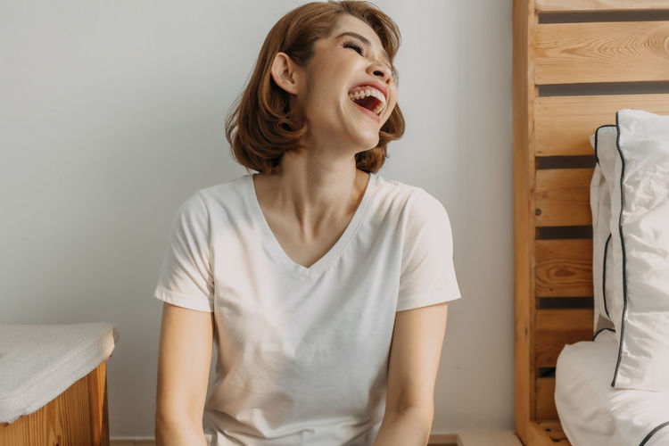 Smiling young woman sitting against wall at home