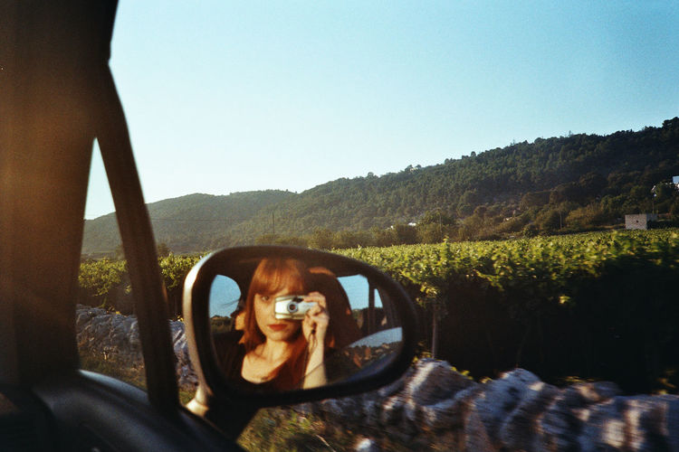 Reflection of woman photographing car on side-view mirror