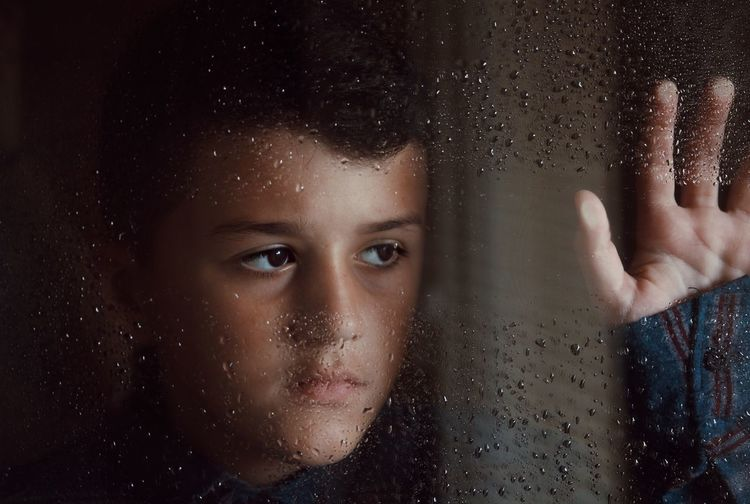Close-up of thoughtful boy looking through wet glass window